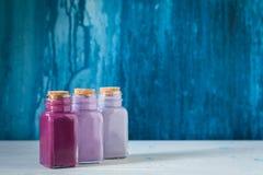 Bouteilles colorées avec des peintures sur le fond concret, concept de dessin Image stock