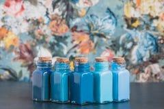 Bouteilles colorées avec les peintures bleues de nuances sur le fond de papier peint, concept de dessin Photographie stock libre de droits