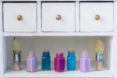 Bouteilles colorées avec les peintures, brosses sur l'étagère en bois, concept de dessin Images stock