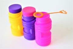 Bouteilles colorées de bulles avec la baguette magique de bulle Photo libre de droits