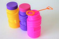 Bouteilles colorées de bulles avec la baguette magique de bulle Photographie stock