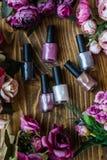 Bouteilles colorées de vernis à ongles sur le fond en bois de Brown photographie stock