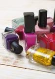 Bouteilles colorées de vernis à ongles sur le fond en bois clair Images libres de droits