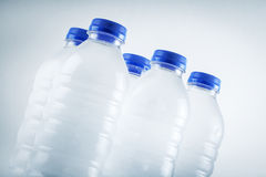 Bouteilles d'eau en plastique humides d'isolement sur le fond blanc Photographie stock
