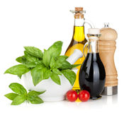 Bouteilles d'huile et au vinaigre d'olive avec le basilic et les tomates Photo libre de droits