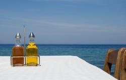 Bouteilles d'huile et de vinaigre d'olive sur la table près de la mer Images stock
