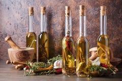 Bouteilles d'huile d'olive avec différentes épices et herbes Photo libre de droits