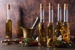 Bouteilles d'huile d'olive avec différentes épices et herbes Images libres de droits