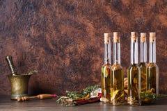 Bouteilles d'huile d'olive avec différentes épices et herbes Photo stock
