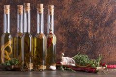 Bouteilles d'huile d'olive avec différentes épices et herbes Photographie stock