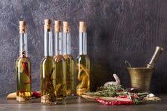 Bouteilles d'huile d'olive avec différentes épices et herbes Photos stock