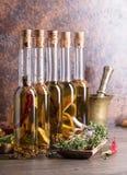 Bouteilles d'huile d'olive avec différentes épices et herbes Photos libres de droits