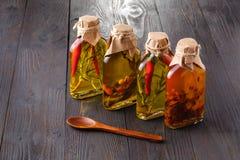 Bouteilles d'huile d'olive vierge supplémentaire avec les herbes aromatiques Photos stock