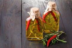 Bouteilles d'huile d'olive vierge supplémentaire avec les herbes aromatiques Photographie stock libre de droits