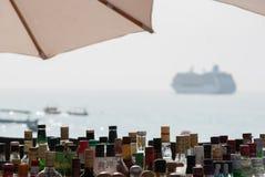 Bouteilles de boisson alcoolisée dans une barre tropicale de plage avec le bateau de croisière photos stock