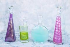 Bouteilles de forme originale différente avec les liquides perlés multicolores photographie stock