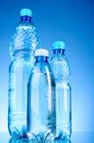 Bouteilles de l'eau sur le bleu Photos stock