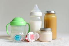 Bouteilles de lait, de purée et d'eau pour le bébé Image stock