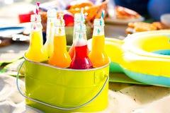 Bouteilles de limonade, se tenant dans un seau vert coloré sur Photographie stock libre de droits