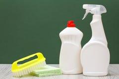 Bouteilles de liquide, de brosse et d'éponges de vaisselle sur le fond vert photographie stock libre de droits