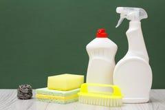 Bouteilles de liquide, de brosse et d'éponges de vaisselle sur le fond vert image stock