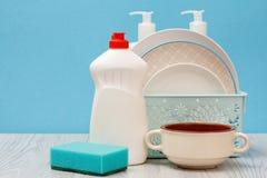Bouteilles de liquide, de plats et d'éponge de vaisselle sur le fond bleu photos stock