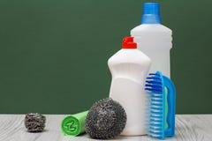 Bouteilles de liquide de vaisselle, de brosse, de sacs de déchets et d'éponges sur le fond vert photo libre de droits