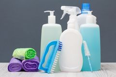 Bouteilles de liquide de vaisselle, de brosses et de sacs de déchets sur le fond gris image libre de droits