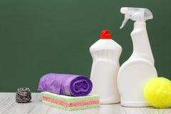 Bouteilles de liquide de vaisselle, de sacs de déchets et d'éponges sur le fond vert photos libres de droits