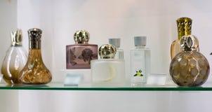 Bouteilles de bouteilles de parfum avec de l'eau toilette sur une étagère en verre image stock