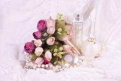 Bouteilles de parfum, rose de blanc et programmes de perles Photographie stock libre de droits
