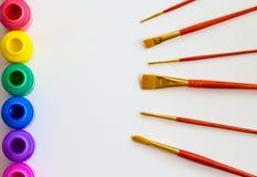 Bouteilles de peinture et pinceaux colorés sur le fond de livre blanc avec l'espace de copie, la vue supérieure/arts et le concep Photo libre de droits