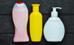 Bouteilles de produits pour la douche Versez le gel, le savon liquide, shampooing sur une table en bois noire Vue supérieure Photographie stock