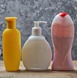 Bouteilles de produits pour une douche sur une étagère en bois contre un mur en béton gris Gel de douche, shampooing, savon liqui Image stock