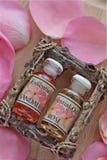Bouteilles de Rose Essence avec des pétales Images stock