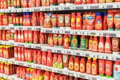 Bouteilles de sauce tomate de ketchup sur l'étagère de supermarché Image libre de droits