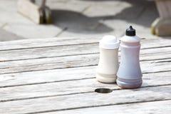 Bouteilles de sel et au vinaigre sur la table en bois Photo stock