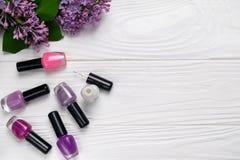 Bouteilles de vernis à ongles sur le fond en bois blanc avec la vue supérieure de fleurs de ressort avec l'espace pour le texte image libre de droits