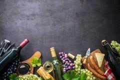 Bouteilles de vin avec des raisins, le fromage, le jambon et des lièges Images libres de droits