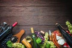 Bouteilles de vin avec des raisins, le fromage, le jambon et des lièges Photos libres de droits