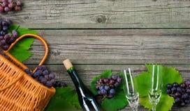 Bouteilles de vin avec des raisins, panier, deux verres à vin sur le fond en bois Images libres de droits