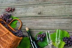 Bouteilles de vin avec des raisins, panier, deux verres à vin sur le fond en bois Photographie stock