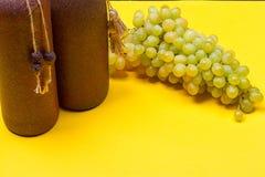 Bouteilles de vin blanc avec des raisins Image stock