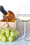 Bouteilles de vin dans une boîte en bois avec un verre de vin et de g blanc Photos libres de droits