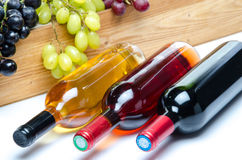 Bouteilles de vin devant une boîte en bois avec des raisins Images libres de droits