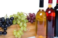 Bouteilles de vin devant une boîte en bois avec des raisins Photo libre de droits
