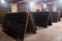 Bouteilles de vin mousseux fermentant dans la cave d'établissement vinicole photo stock