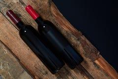 Bouteilles de vin rouge compos?es sur les rondins en bois au-dessus du fond noir photos libres de droits