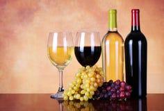 Bouteilles de vin rouge et blanc avec des raisins frais Photo libre de droits