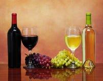 Bouteilles de vin rouge et blanc avec des raisins frais Photographie stock libre de droits